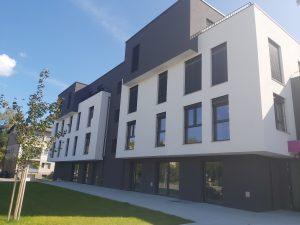 Stanovanjski blok z belo in sivo fasado ter zelenico.