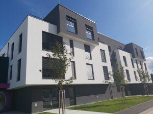 Trinadstropni stanovanjski blok z belo in sivo fasado ter zelenico pa vhodom.