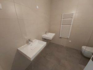 Kopalnica v stanovanju z dvojnim umivalnikom, tuš kabino in WC školjko.