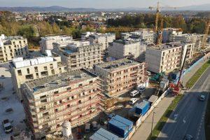 Slika je posneta z dronom in prikazuje večstanovanjske objekte. Objekti so strnjeni in so v različnih fazah izgradnje.